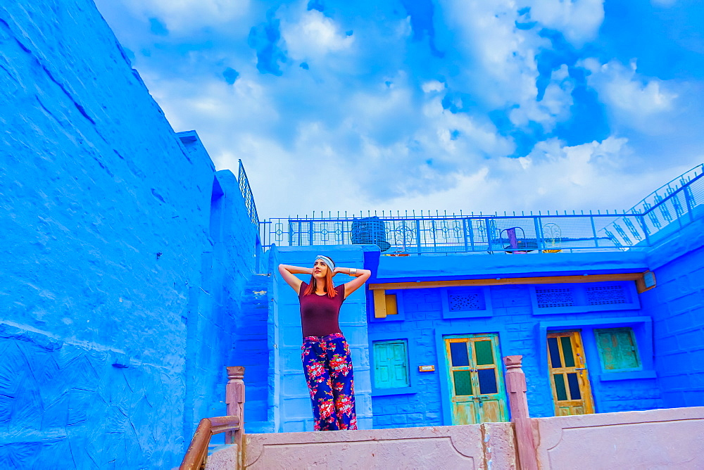 Woman stands on the blue rooftop of Rani Mahal Hotel, in Jodhpur, the Blue City, Rajasthan, India, Asia