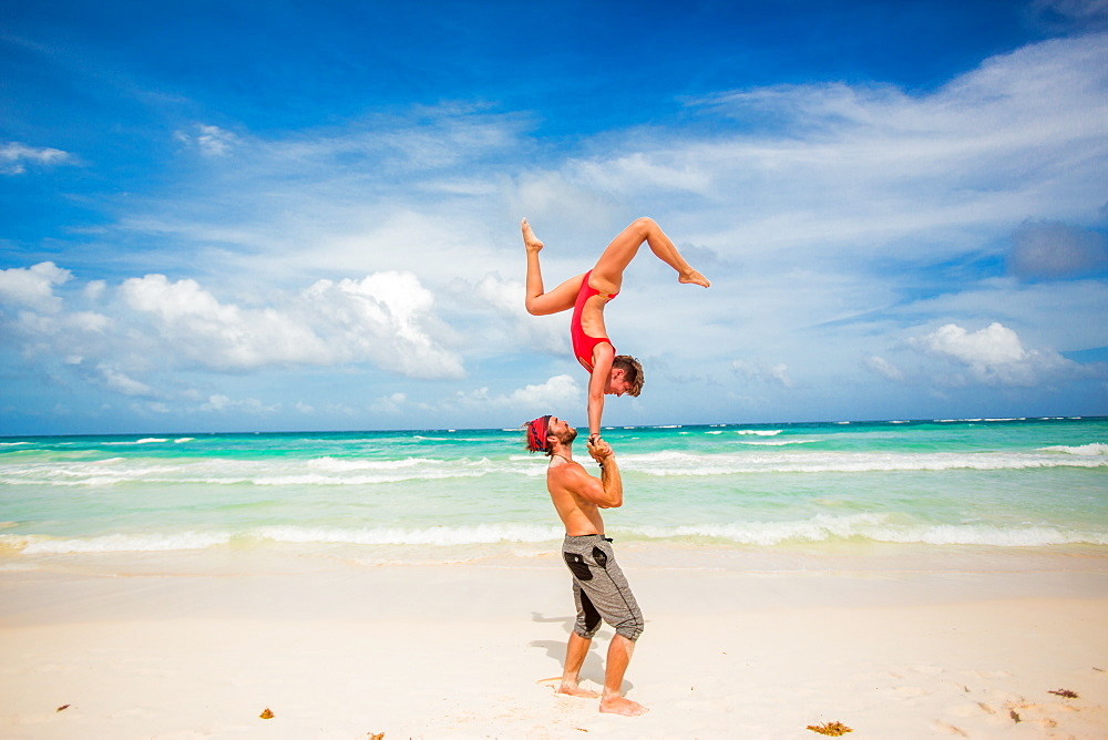 Acrobatic couple balancing together on the beach of Tulum, Mexico, North America