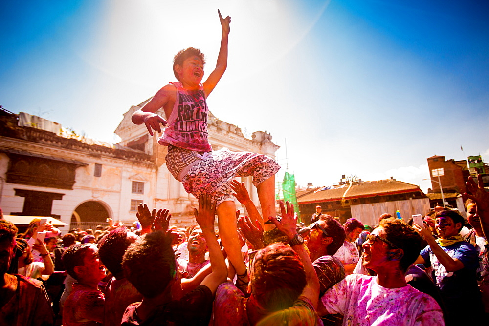 Boy being thrown in the air during the Holi Pigment Throwing festival in Durbar Square, Kathmandu, Nepal, Asia