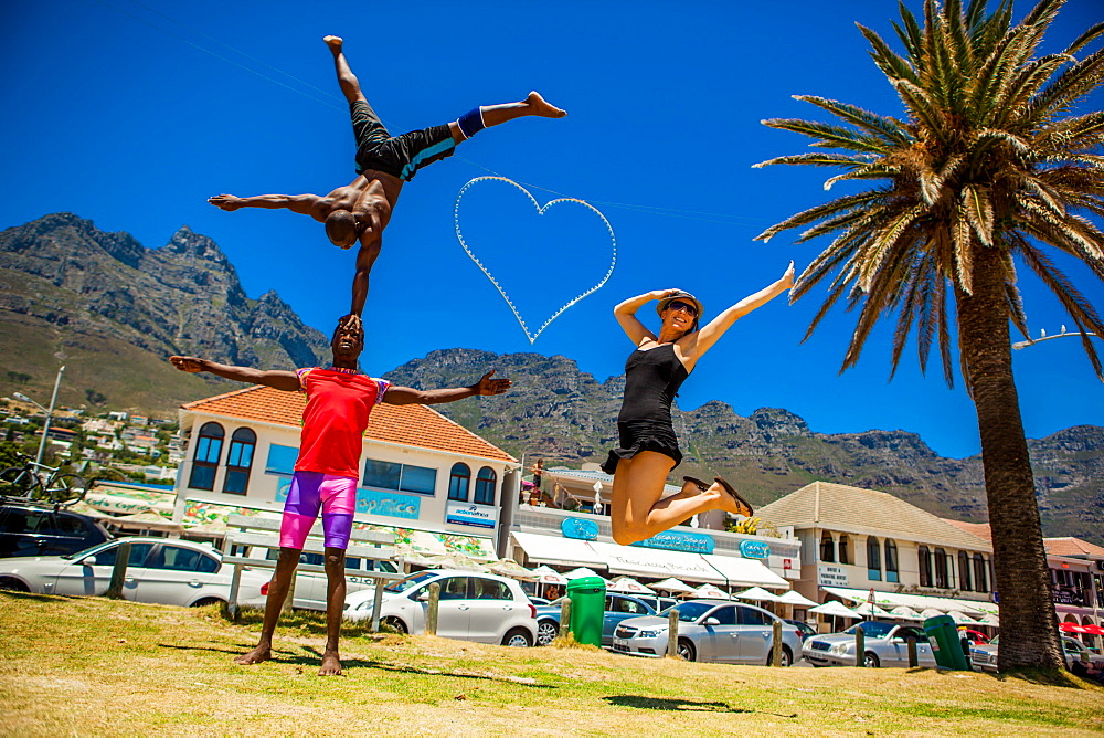 Laura Grier jumping with African acrobats, Camps Bay, South Africa, Africa