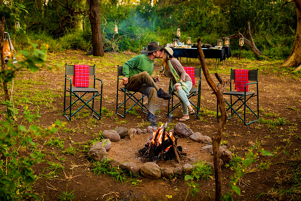 Couple kissing by a safari camp campfire in Zululand, South Africa - 1218-722