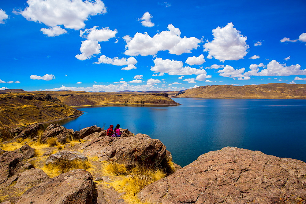 Two people sitting on the edge of Lake Titicaca, Peru, South America