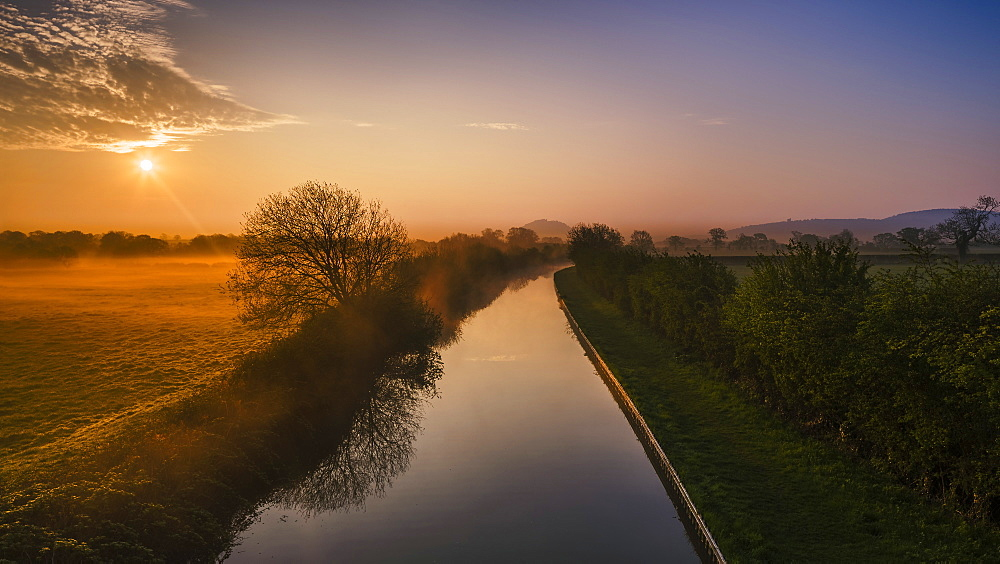 The Shropshire Union canal leads through the Cheshire plain to Beeston Castle and the Peckforton sandstone ridge at sunrise, Cheshire, England, United Kingdom, Europe