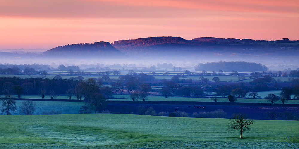 Dawn illuminates Beeston and Peckforton castles on the Peckforton sandstone ridge with mist lying on the Cheshire plain below, Cheshire, England, United Kingdom, Europe - 1219-120