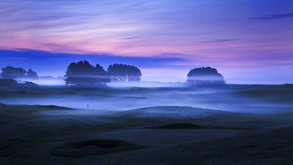 Spring mist lies in the cold undulating valleys across the greens and fairways at Delamere Forest Golf Club, Cheshire, England, United Kingdom, Europe