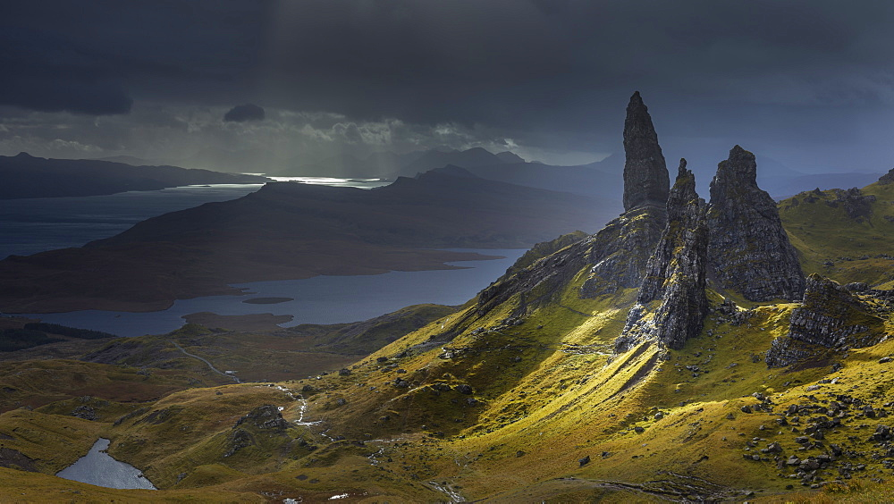 A burst of light briefly illuminates the pinnacles surrounding the Old Man of Storr against an approaching storm, Isle of Skye, Inner Hebrides, Scotland, United Kingdom, Europe