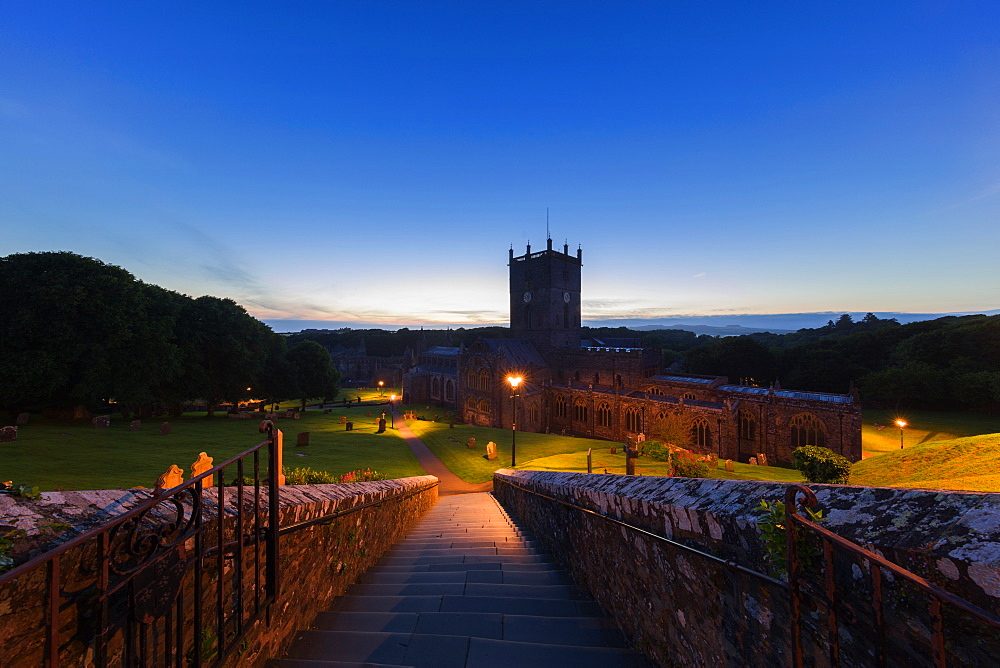 The historic St David's cathedral and Bishops Palace nestled in a natural valley at dusk in Pembrokeshire.