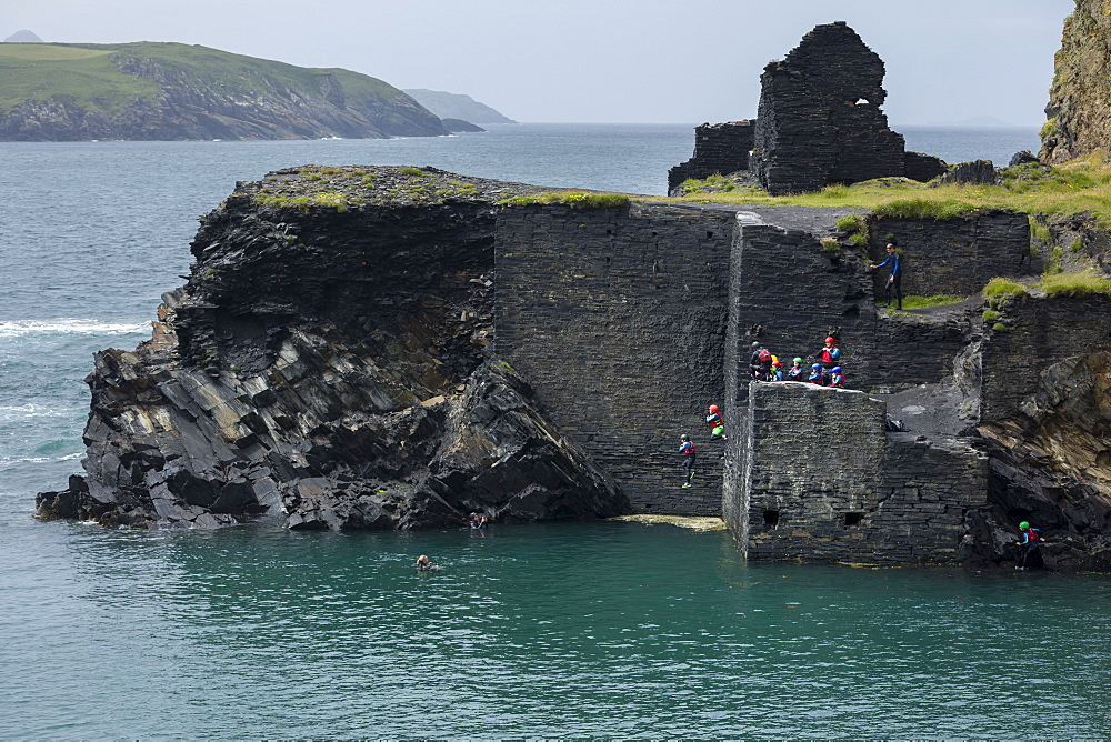 Coasteering activity with people jumping from the former quarry building at the Abereiddy blue lagoon, Pembrokeshire, Wales, United Kingdom, Europe - 1219-209