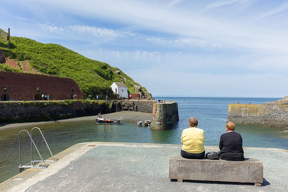 Two ladies on a bench at Porthgain harbour as the Pembrokeshire coast path extends up the cliffs beyond, Wales, United Kingdom, Europe - 1219-214