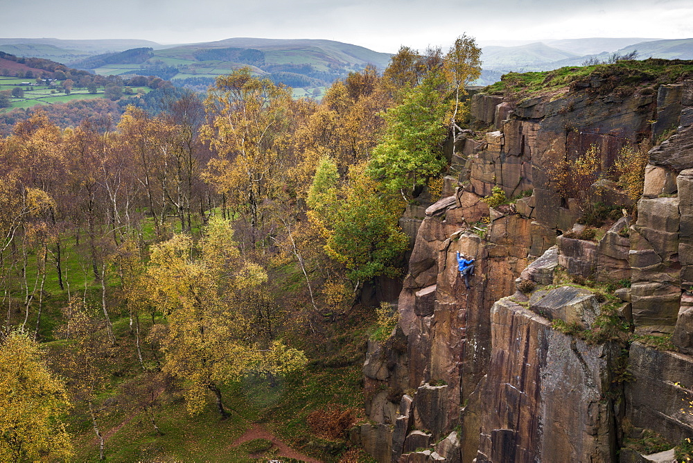 A rock climber ascends a cliff face formed by historic quarrying at Bole hill quarry on an autumn day in the Peak District, Derbyshire, England, United Kingdom, Europe - 1219-219