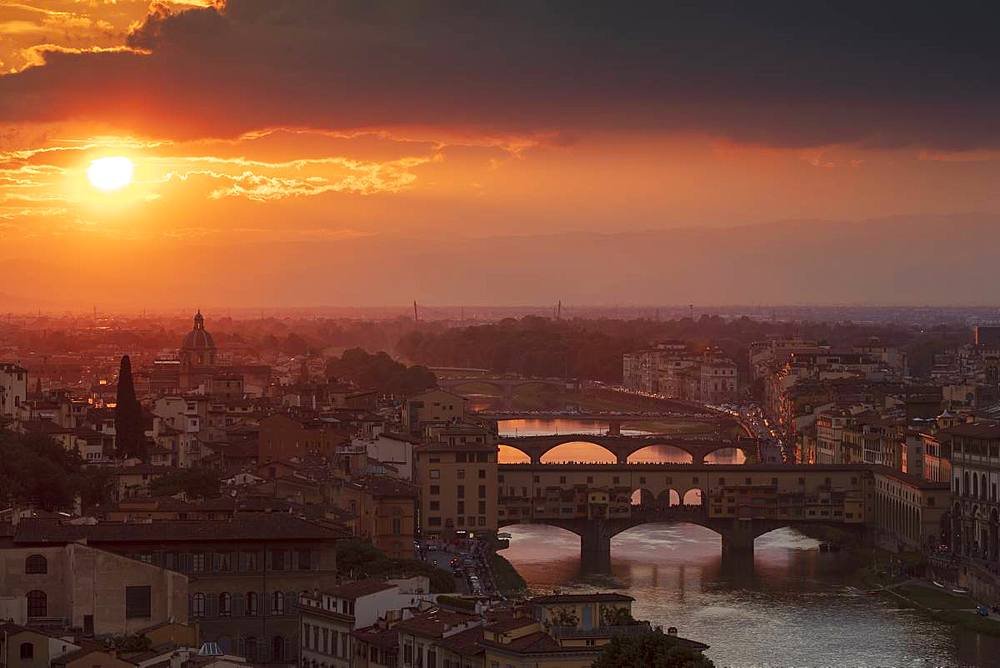 Sun setting behind the city of Florence with the Ponte Vecchio and Ponte Santa Trinita bridges over the Arno River, Florence, Tuscany, Italy, Europe - 1219-248