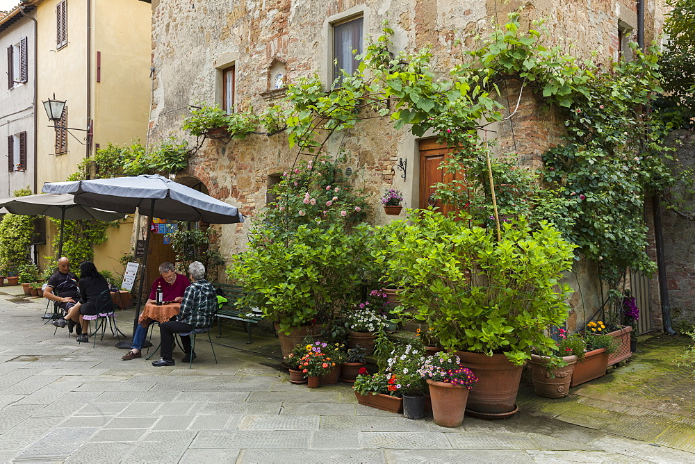 People sitting outside at a restaurant within a small courtyard surrounded by flowers in Pienza, Tuscany, Italy, Europe - 1219-259