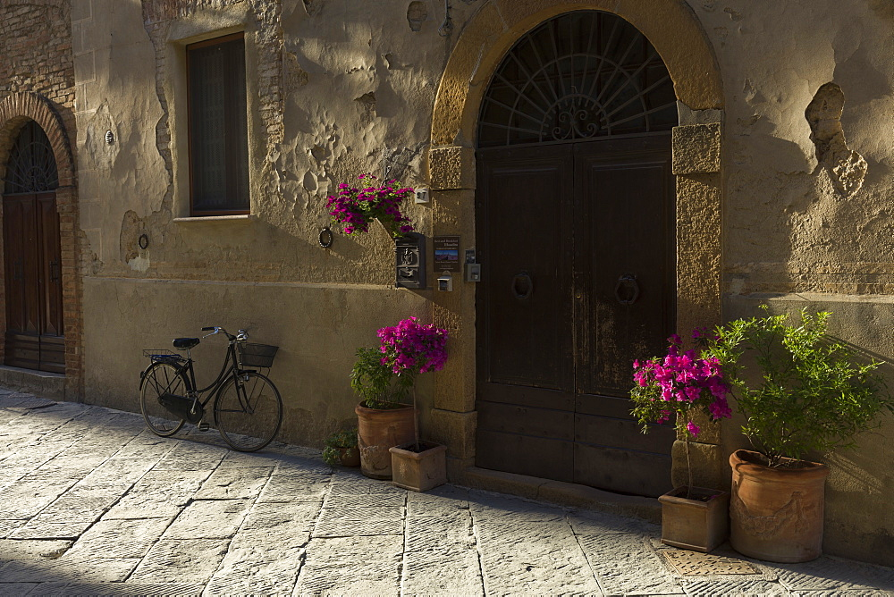 A bicycle and flowers outside a building in Pienza, Val D'Orcia, Tuscany, Italy, Europe - 1219-260