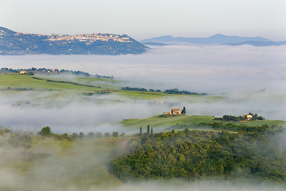 Looking across the Val d'Orcia to Montalcino perched on a hill above cloud and fog lingering in the valley below