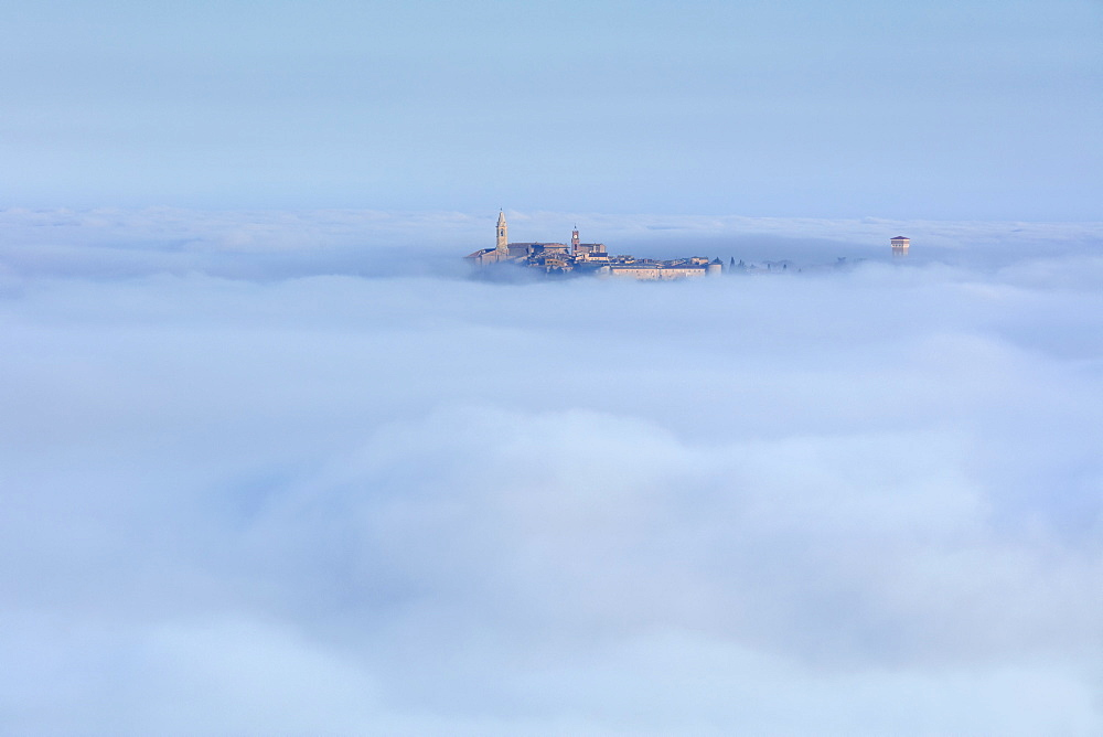 Pienza's Clock Tower and Cathedral Bell Tower rise above the clouds and fog that covers the Val d'Orcia below