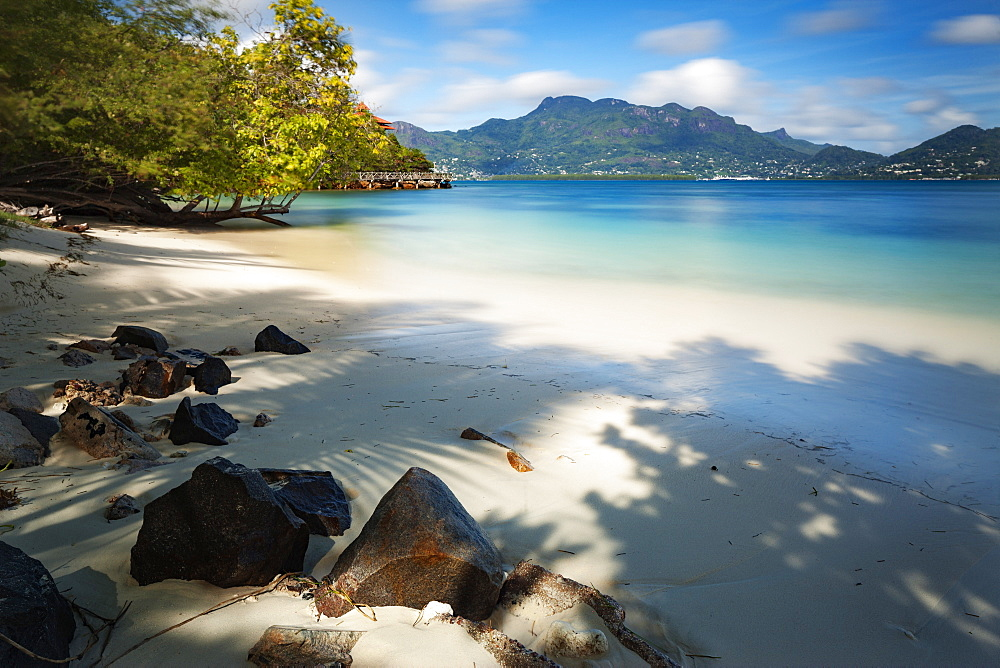 A deserted Seychelles beach with the calm still waters of the Indian Ocean beyond, Seychelles, Indian Ocean, Africa