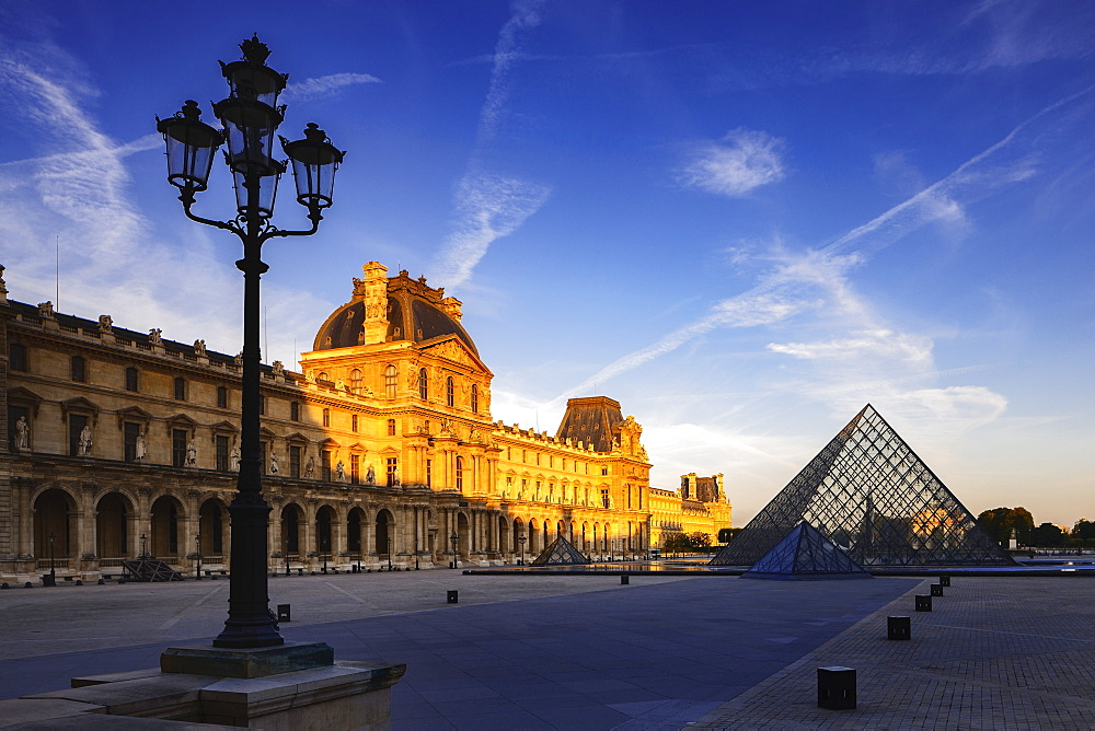 Dawn light illuminates the Louvre Palace bordering the Napoleon Courtyard and Louvre Pyramid, Paris, France, Europe