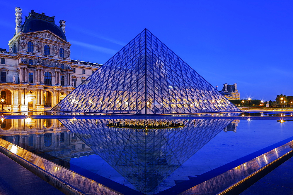 The Louvre Pyramid and Palace reflected in a still pool within the Napoleon Courtyard at twilight, Paris, France, Europe