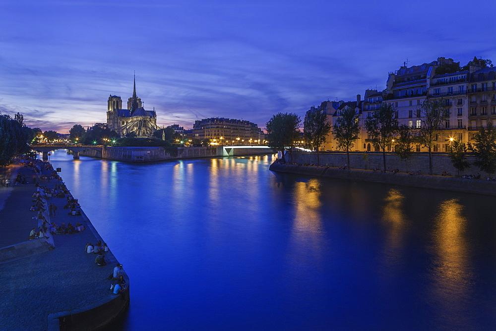 Groups of Parisians and tourists line the banks of the River Seine with Notre Dame lit against the dusk sky on the Ile de la Cite, Paris, France, Europe