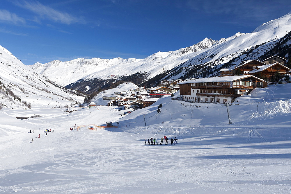 Groups of skiers enjoying the winter conditions with the village of Obergurgl and Otztal Alps beyond, Tyrol, Austria, Europe