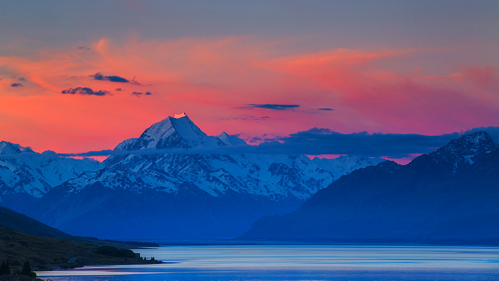 The last rays of the setting sun strike the peak of Aoraki (Mount Cook) beyond the shores of Lake Pukaki in the Southern Alps, UNESCO World Heritage Site, Canterbury, South Island, New Zealand, Pacific