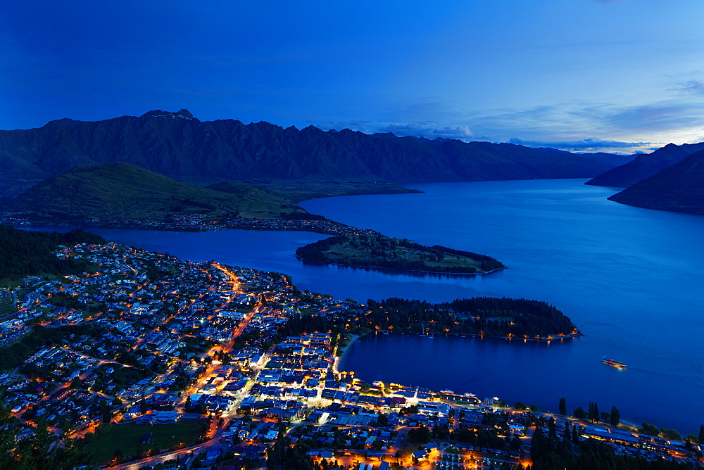 Queenstown at dusk on the shore of Lake Wakatipu with the Remarkables mountain range beyond, Otago, South Island, New Zealand, Pacific