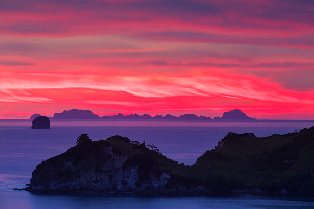 The sky appears on fire as dawn light seeps through the clouds beyond the Alderman Island and Coromandel Peninsula, Waikato, North Island, New Zealand, Pacific