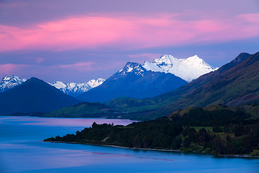 Snow covered Mount Earnslaw within New Zealand's Southern Alps set against a pink early evening sky beyond Lake Wakatipu, Otago, South Island, New Zealand, Pacific