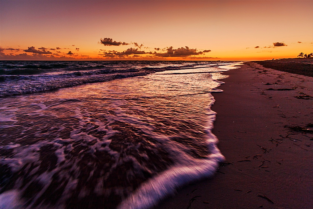 Waves roll onto the beach as dawn breaks beyond the Hicacos peninsula and long stretch of beach at Varadero, Cuba, West Indies, Caribbean, Central America - 1219-84
