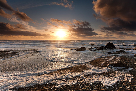 Storm surf and hills of sea foam under a sunset skyscape at Tyn Tywyn beach, Rhosneigr, West Anglesey, Wales, United Kingdom, Europe