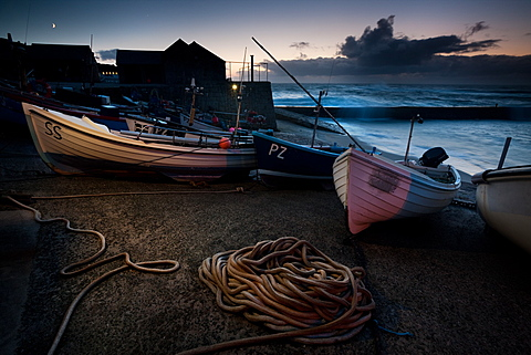 New moon rises as heavy weather moves closer and waves break over the quay at dusk at Sennen Cove, South West Cornwall, England, United Kingdom, Europe