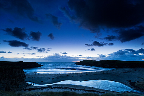 Lines of waves roll in at dusk at Cable Bay surfing beach, West Anglesey, Wales, United Kingdom, Europe