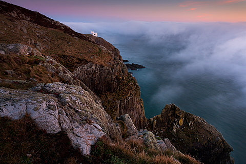 A temporary clearing in thick fog during a temperature inversion over the Irish Sea at dusk, South Stack, RSPB tower on clifftop, Anglesey, Wales, United Kingdom, Europe