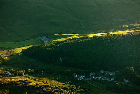 Late afternoon sunlight floods up from the Nantlle Valley as the village of Rhyd Ddu nestles in the shadowy woodland hillside, Gwynedd, Wales, United Kingdom, Europe