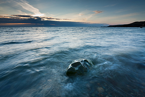 Waves flow over a face-shaped rock in the sea at sunset, Porth Swtan, North Anglesey, Wales, United Kingdom, Europe