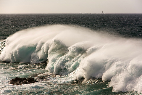 20 ft Atlantic waves over reef at Cape Cornwall, St. Just, creating white horses on wave faces, and Longships Lighthouse in distance, Cornwall, England, United Kingdom, Europe