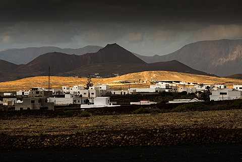 A short burst of sunshine on a small hillside amongst the black-earthed volcanic landscape of Tinajo in central Lanzarote, Canary Islands, Spain, Europe