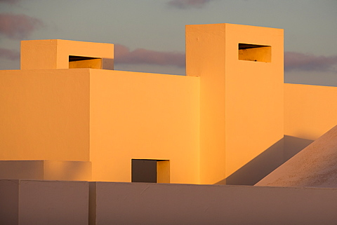 Evening sunlight catching the rooftops of the single storey buildings in Playa Blanca, Lanzarote, Canary Islands, Spain, Europe