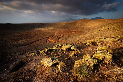 Approaching weather front over the southern volcanic peaks of Lanzarote seen from the Montana Roja crater in Playa Blanca, Lanzarote, Canary Islands, Spain, Europe