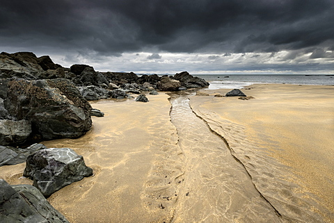 A stream cuts down the beach, carving beautiful curves through virgin sand, black clouds stall overhead, Rhosneigr, Anglesey, Wales, United Kingdom, Europe