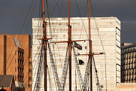 An old tallship in Albert Dock contrasts strikingly against the huge modern developments behind, Liverpool, Merseyside, England, United Kingdom, Europe