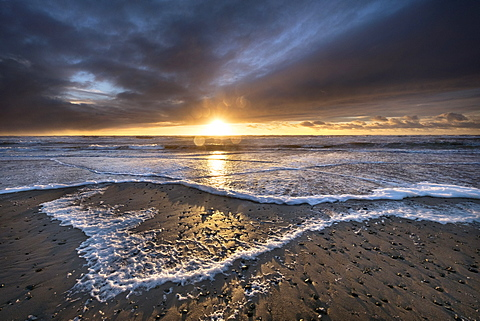 Waves pile foam crescents on the high tide mark at sunset in winter at this West Anglesey beach near Rhosneigr, Anglesey, Wales, United Kingdom, Europe