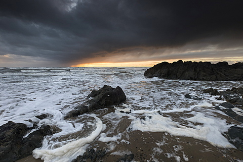 Streams of wind-blown foam from successive winter storm waves on the incoming tide at Rhosneigr, West Anglesey, Wales, United Kingdom, Europe