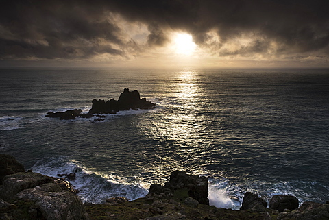 Land's End in a winter sunset with sunburst under a blanket of winter storm clouds and deceptively calm seas nevertheless, Cornwall, England, United Kingdom, Europe