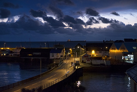 Dawn appears over the horizon from Penzance harbour, and Scillonian ferry in dry dock, Penzance, Cornwall, England, United Kingdom, Europe
