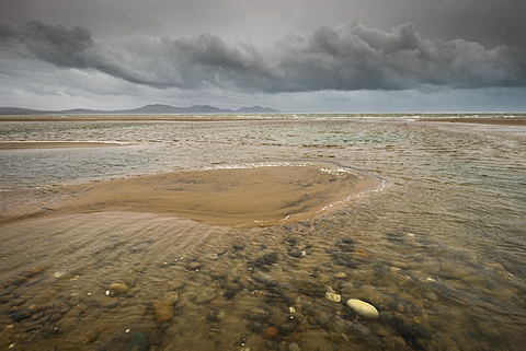 Strong winds from Storm Imogen ruffle pools at Llanddwyn Beach, West Anglesey, and dark clouds build on the the horizon, Anglesey, Wales, United Kingdom, Europe