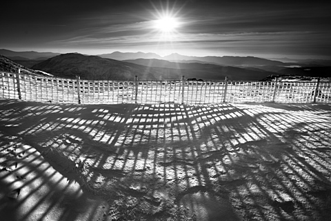 Long shadows cast by a fence coated wind driven rime frost formations on Arening Fawr, Snowdonia, Wales, United Kingdom, Europe