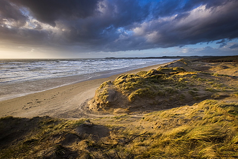 Sunlight in stormy weather and gale force winds at Llanddwyn beach, West Anglesey, Wales, United Kingdom, Europe