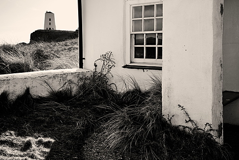The old lighthouse of Twr Mawr beyond small pilot cottages on Llanddwyn Island, Anglesey, Wales, United Kingdom, Europe