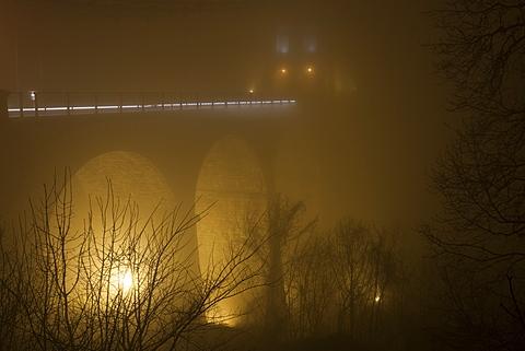 Night fog envelops Thomas Telford's 100ft high Menai Suspension Bridge, built in 1826, between Anglesey and mainland Wales, Wales, United Kingdom, Europe
